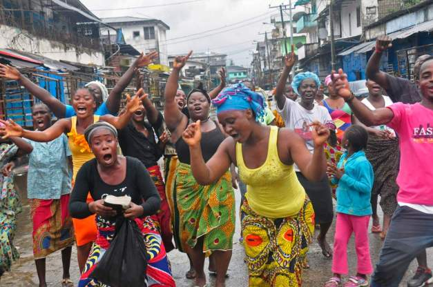 People celebrate in a street outside of West Point slum in Monrovia, Liberia, Saturday, Aug. 30, 2014. Crowds cheer and celebrate in the streets after Liberian authorities reopened a slum where tens of thousands of people were barricaded amid the countryís Ebola outbreak. The slum of 50,000 people in Liberia's capital was sealed off more than a week ago, sparking unrest and leaving many without access to food or safe water. (AP Photo/Abbas Dulleh)