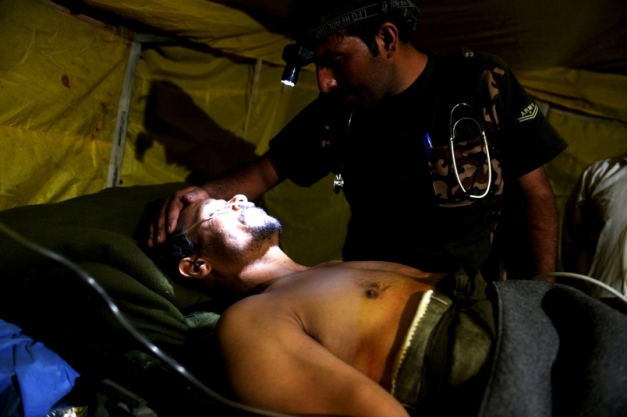 Injured Afghan policeman examined by Afghan Army doctor August 2015